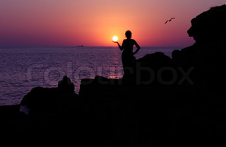 silhouette of girl holding sun at sunset near sea