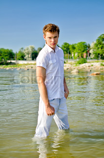 Handsome young guy standing in the sea in jeans
