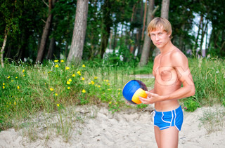 Young man posing with the ball on the beach