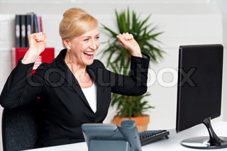 Excited corporate lady looking at computer screen