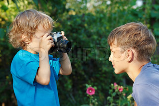 Little cute blond boy with a camera shoots her brother