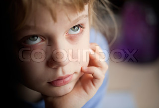 Little girl is boring and misses for something. Closeup portrait with shallow depth of field