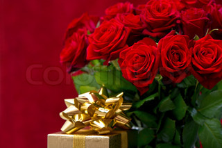 red roses and golden gift with ribbon