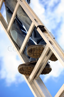 closeup of worker's legs and feet standing on metal ladder diagonally pointing up in the sky