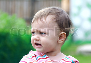 Beautiful sad baby crying on nature green summer background