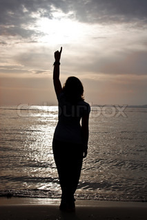 A silhouette of a beautiful girl against the sunset.