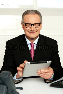 Senior executive sitting with tablet pc in hands