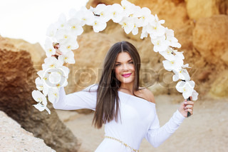 Portrait of beautiful brunette woman in white dress posing over sea coast with white flowers