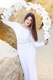 Portrait of beautiful brunette woman in white dress posing over sea view with white flowers