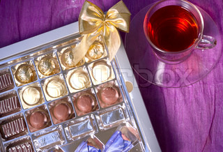 A transparent glass cup of tea beside the box of sweets
