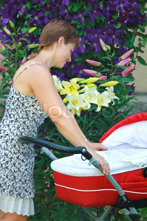 Young mother looking on new born baby in red pram and smiling with love