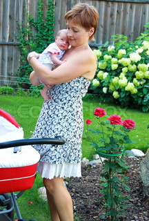 Happy young mother holding new born baby girl on the hands on nature