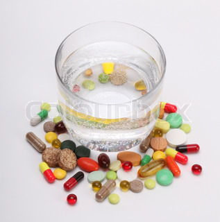 vitamins, tablets and pills and glass of water