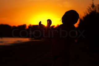 little girl holding in hands the setting sun