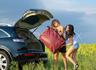 Women loading a heavy bag into car