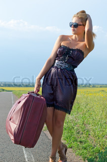 Woman with suitcase on rural road