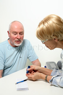 diabetes nurse taking blood from senior patient's finger