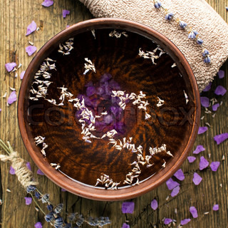 Bowl of pure water and lavender petals on the old wooden surface. Spa treatments composition