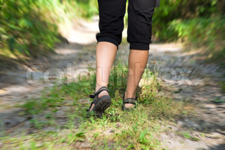 A woman walking on a cross-country trail in the woods