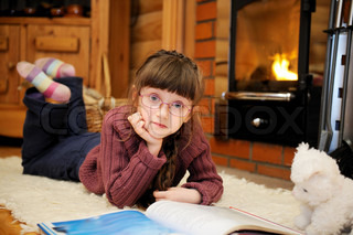 Child girl is reading in front of fireplace