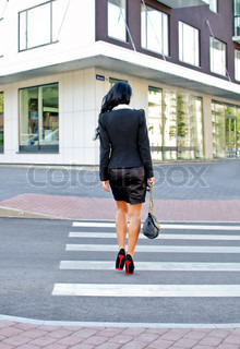 Woman crossing the street Back view