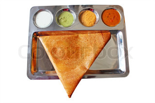 Appetizing and delicious traingular Indian masala dosa in golden brown color with 3 types of chutney and sambhar served in a steel plate This thin masala dosa is more popular in chennai and tamilnadu