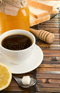 coffee, honey, lemon and bread on table