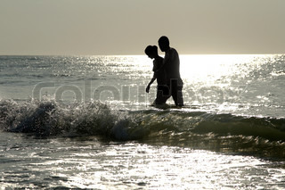 Young couple in the sea at sunrise