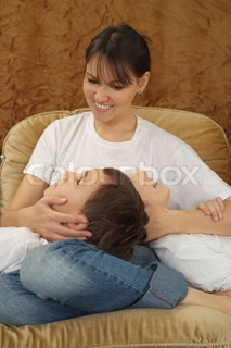 A beautiful Caucasian mom with her son sitting on the couch