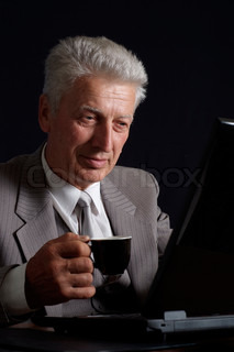 Imposing old man in suit with a cup of coffee