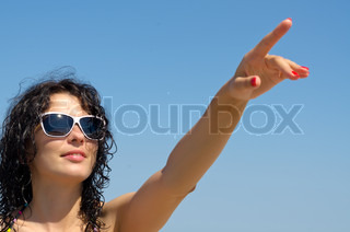 Woman in sunglasses pointing to sky