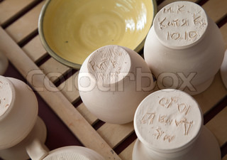 Pottery examples with artists initials and dates on the shelf in the art school