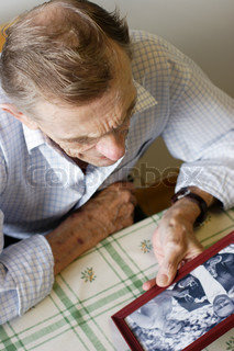 old man sitting at table looking at photo in his hand, from above
