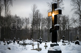 Orthodox cemetery with big black cross shining in the morning sunlight