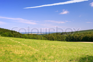 Landscape with the field and followed by an aircraft in the blue sky