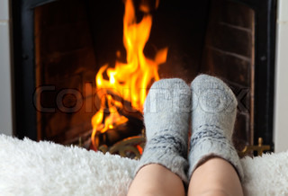 Children's feet are heated by the fireplace