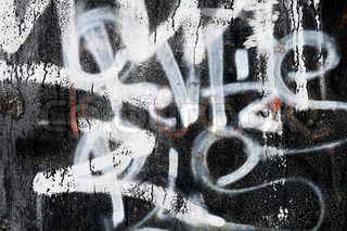 Abstract urban background texture: old black painted metal wall with a graffiti on it