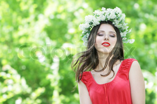 young beautiful woman in floral wreath on natural background