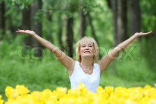 outdoor portrait of happy middle-aged woman on natural background