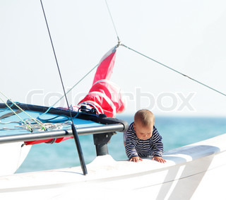 young child on board of ship on sea background