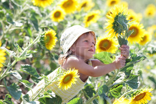 young happy child girl in sunflower field
