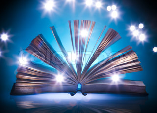 Open old book, mystical blue light at background