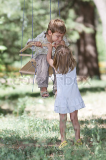 two happy children on swing on natural background