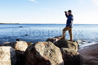 senior man with warm clothing standing on rocky shore watching the sea
