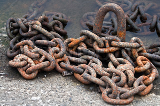 Rusty ship chain on the stone coast