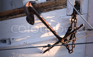 Close up photo of an old ship's mooring anchor on white painted hull