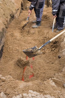 Workers installing sewer pipe in sandy trench