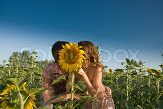 Loving couple and sunflower on the field