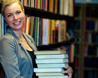 Cheerful librarian or student standing inside a library carrying a stack of large books either for education and research or inventory that has to be replaced on the shelves
