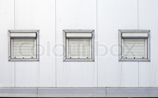Texture of industrial building wall with three closed rectangle windows with jalousies and numeration